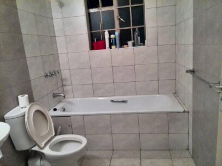 Toalett, dusch och badkar med varmt vatten.