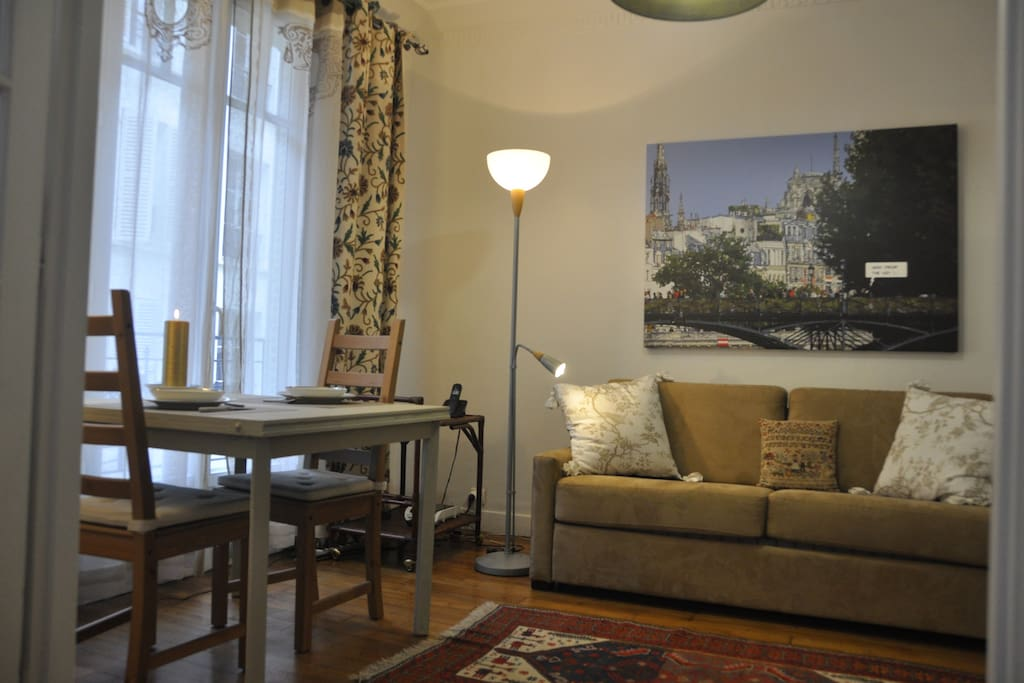 The living room with a new convertible sofa bed !... table for 4 people and a very nice picture of romantic Paris !...