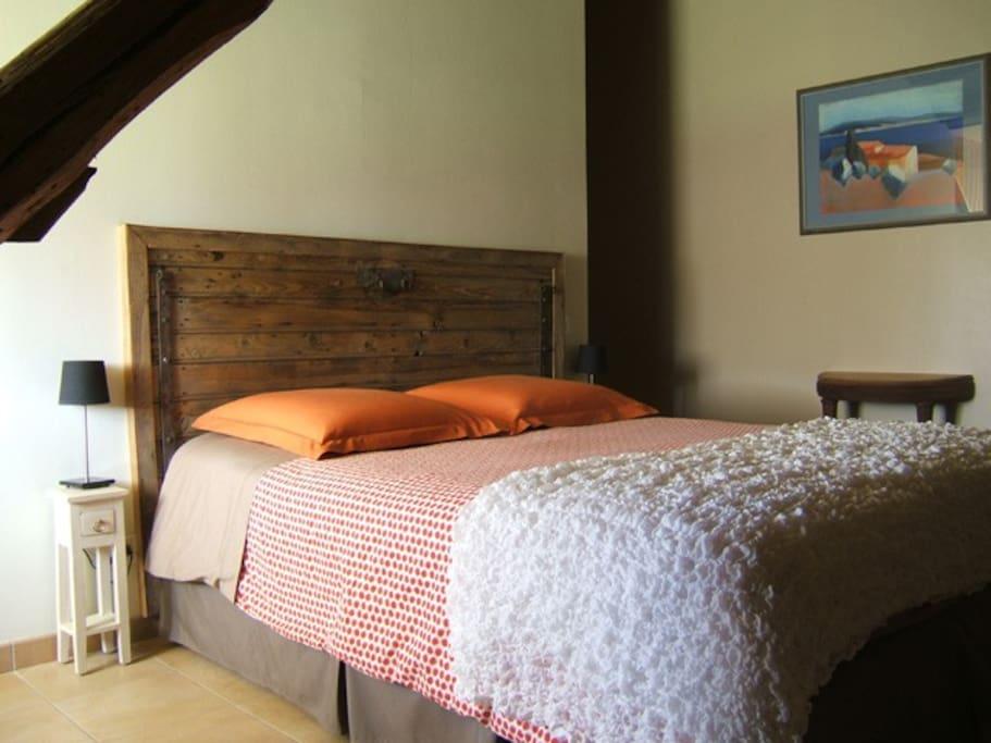 Tête de lit avec une porte de l'ancienne ferme. Sous la charpente.Chambre Avitus