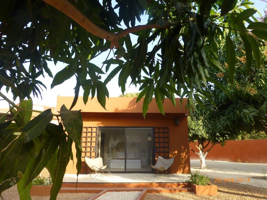 un bungalow, chambre salle de bain et dressing au milieu du jardin