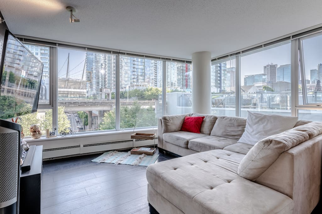 "floor to ceiling wide windows from living room with comfortable clean sectional couch and 60"" flat screen TV"