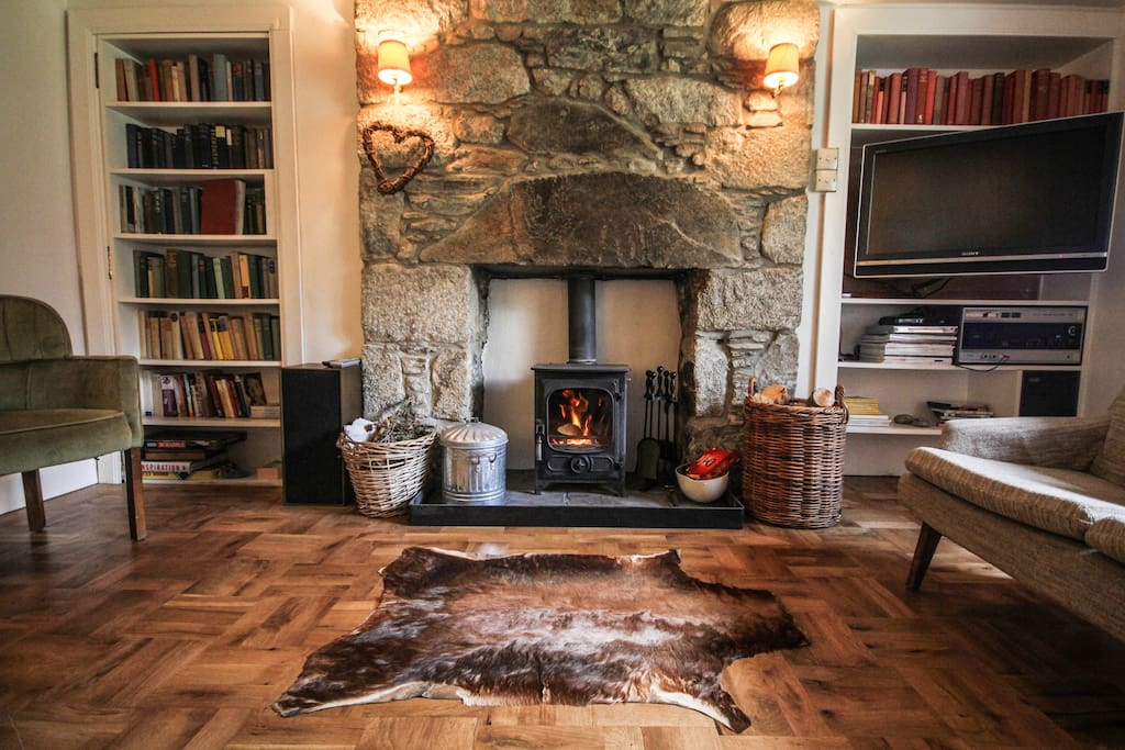 Cosy living room with oak parquet and log burning stove.