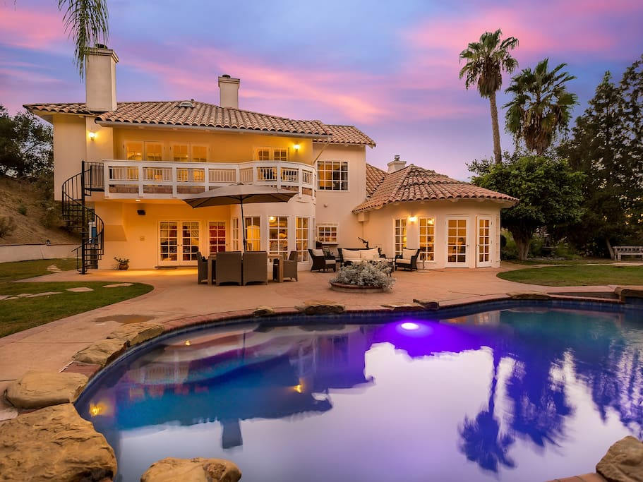 A twilight view of the gorgeous backyard. It features a swimming pool, jacuzzi hot tub, cushioned seating, a 6 seat teak dining set, plenty of yard space and a wisteria-covered gazebo.