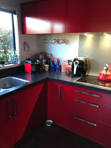 Jalapeño red kitchen with Nespresso machine cooking facilities and loads of utensils etc.