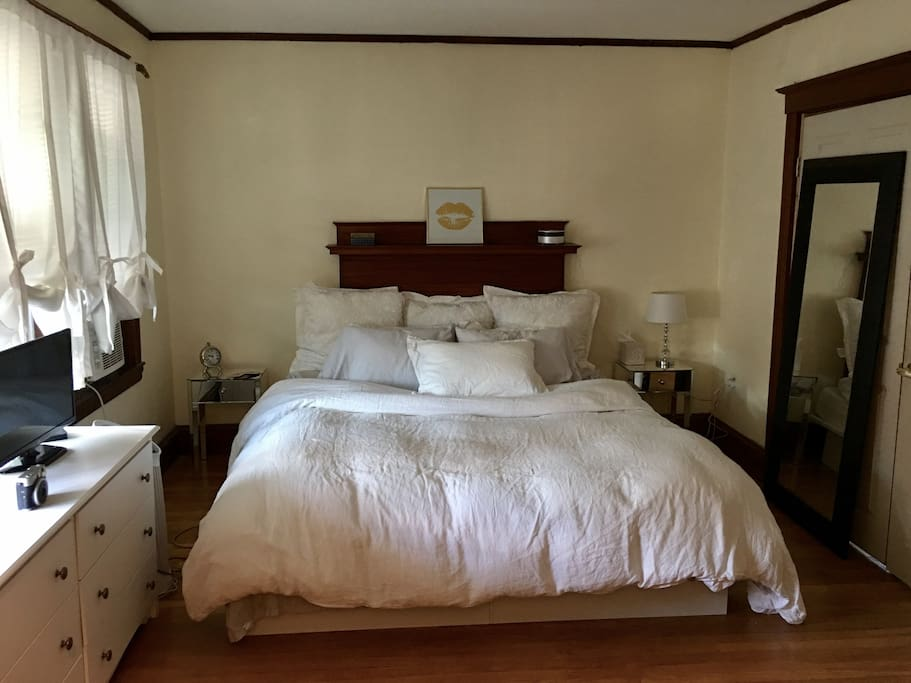 Enter the house into a huge big bedroom! 3 windows! Tons of sunlight! King bed, linen sheets, down pillows, dresser, mirror, tv.