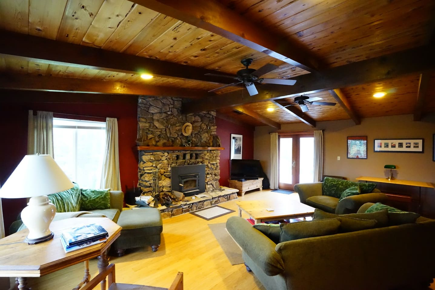 Black Oak Hill living room has vaulted cedar ceiling, stone fireplace with wood stove (available Nov-March), and dedicated puzzle table (photo by Bryant Liu)
