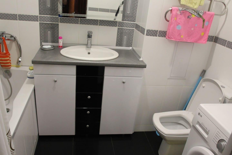 Bathroom with hot tub and washing machine