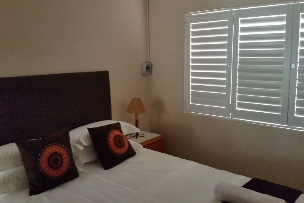 Bedroom with queen size bed and shutters on windows