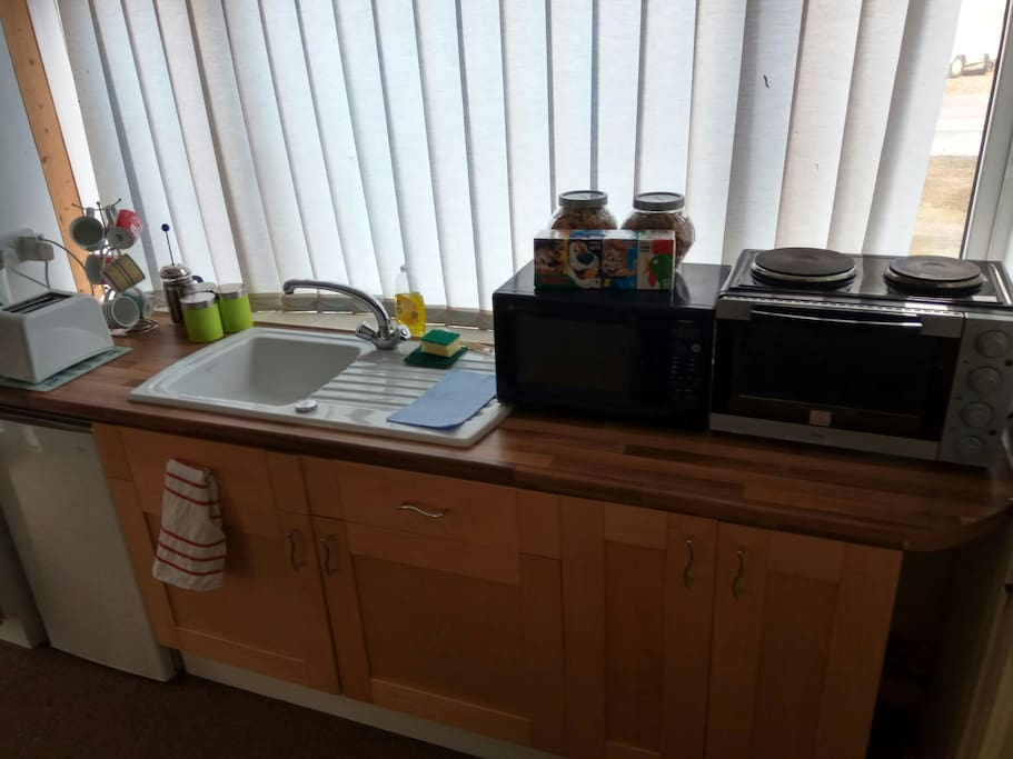 Kitchen area with various cooking options and free breakfast cereals,Tea and coffee.