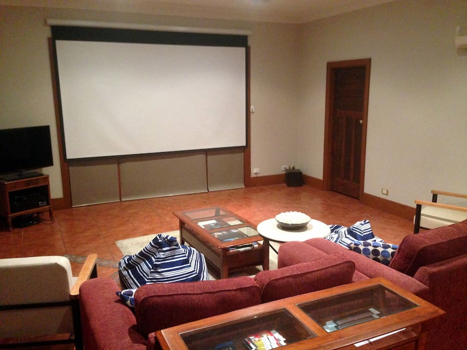 """Lounge in Home Cinema mode, featuring 133"""" screen and 5.1 surround sound."""