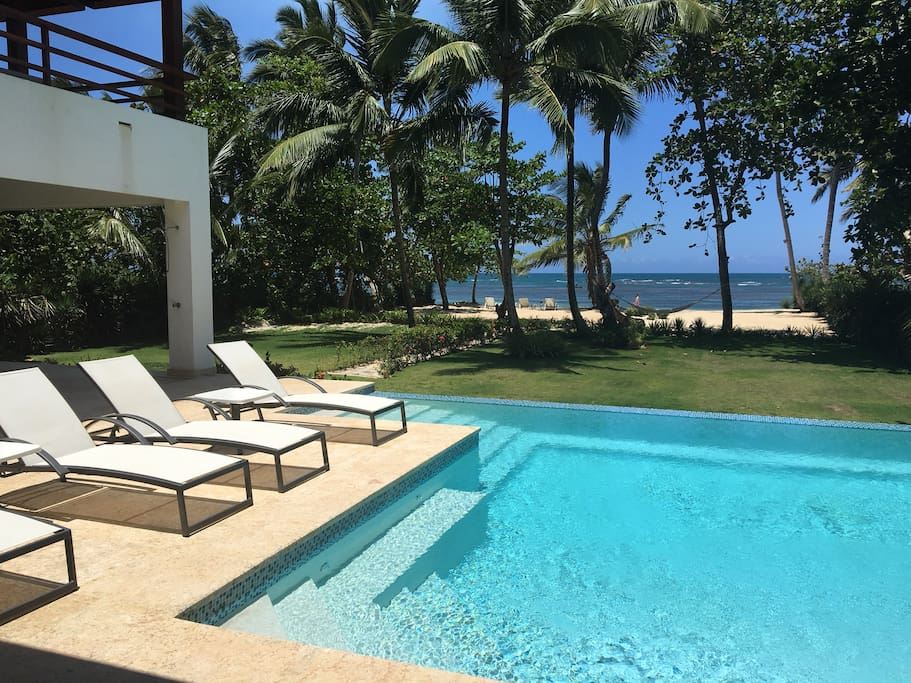 Infinity pool with built in seating looks out on private yard and beach.