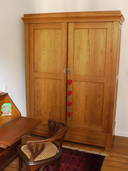 the room for rent has an antique writing desk and wardrobe