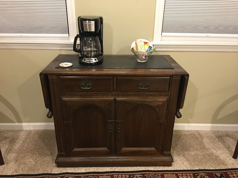 In room buffet table with coffee maker and snacks.  Sides pull up to extend for workspace on either side.