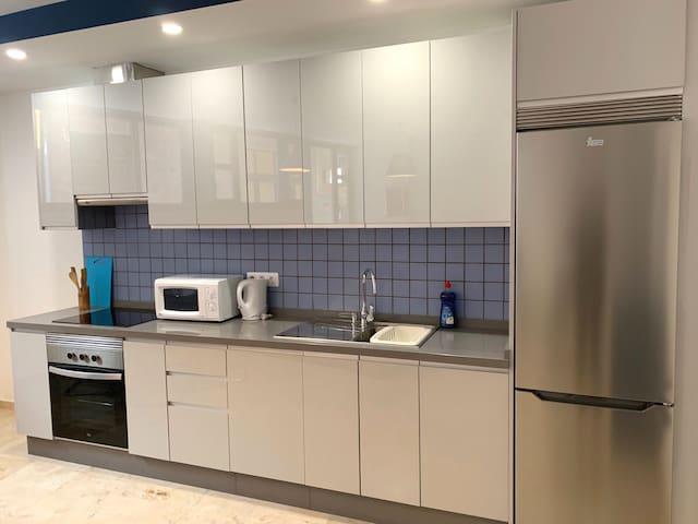 Full kitchen with oven, hob, microwave, kettle, toaster, dishwasher, fridge/freezer.