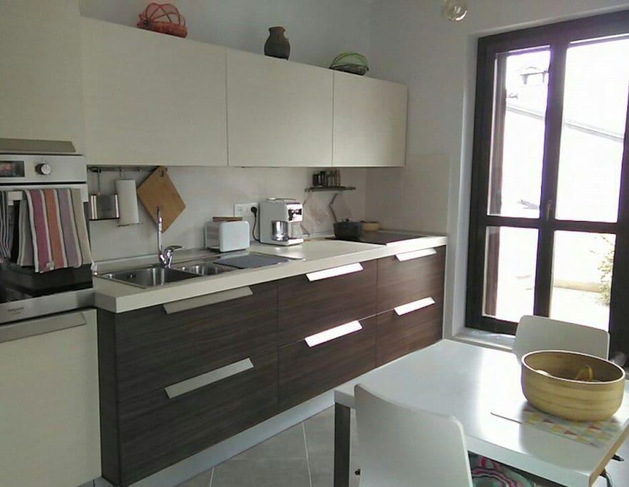 cuisine ouvrant sur terrasse et balcon avec lave vaisselle, four, plaque induction