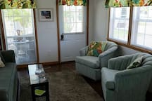 Living room with full size couch and two chairs. TV has local channels and also has Netflix and Hulus at no extra charge.