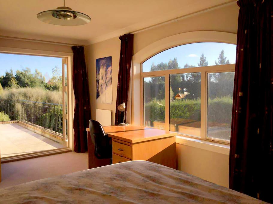 The bedroom is on the second level, with a balcony that overlooks the main garden.