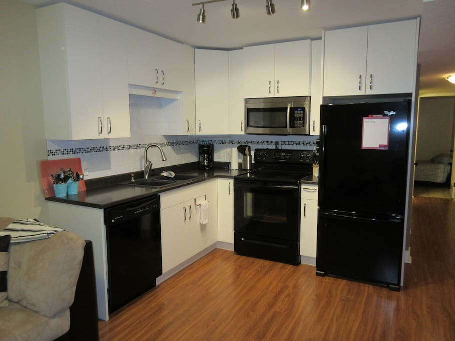 Full kitchen with toaster, kettle, dishes and cookware