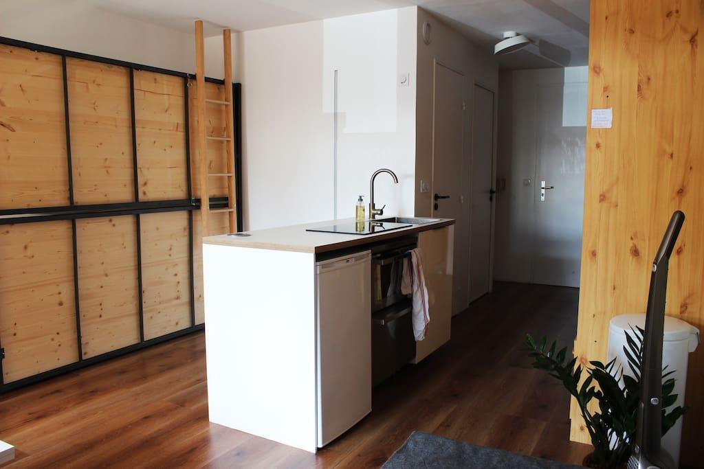 Le bloc cuisine est équipé bien évidement d'un évier, d'une plaque  induction et d'un frigo mais aussi d'un lave-vaisselle, d'un four et d'une multiprise encastrable pour brancher l'électroménager.