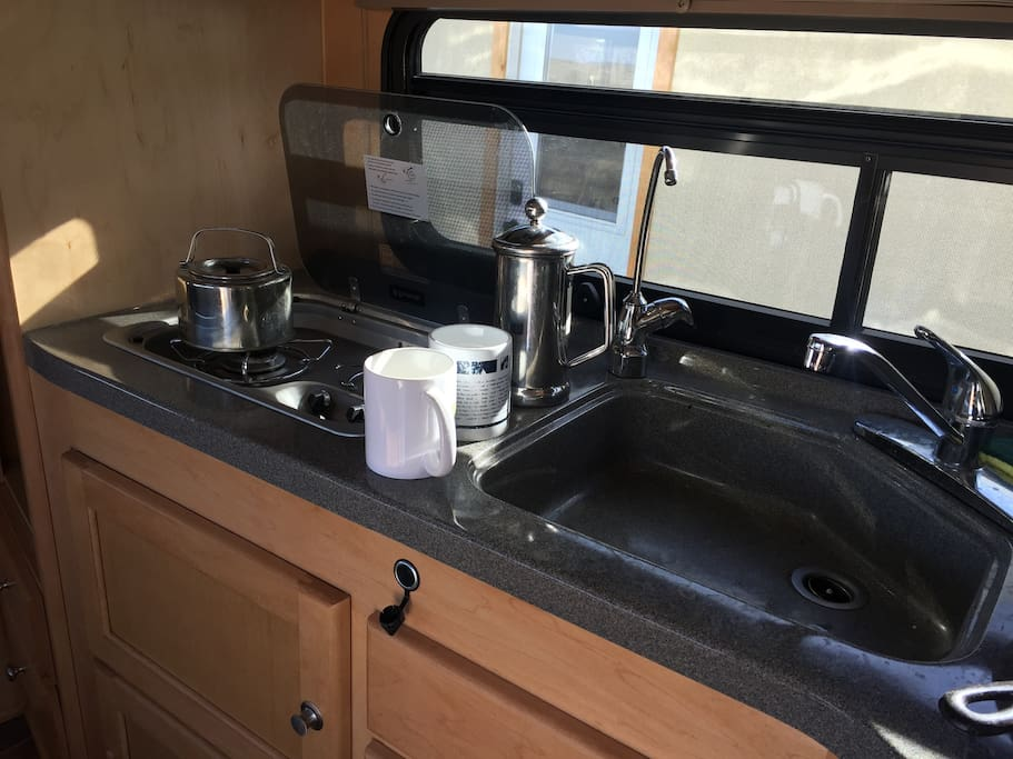 Small but super functional Kitchen includes two gas burners, fridge, cast iron skillet, french press and other kitchen essentials.