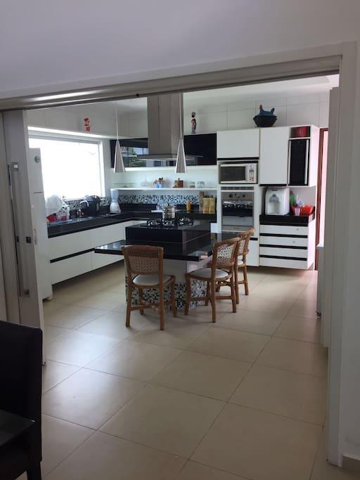 Sala de jantar anexo a cozinha inspirado no estilo americana, com todos os utensílios e eletrodomésticos.