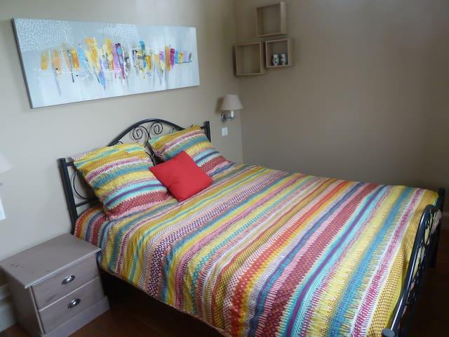 Chambre avec lit double, commode, chevet, volets roulants