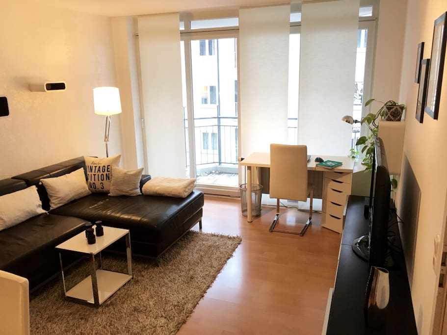 Große Dreisitzer-Couch, kleiner integrierter Arbeitsplatz und Balkon zur ruhigen Seitenstraße. / Large sofa, integrated workplace and balcony to a quiet residential street.