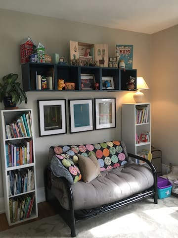 Living Room, with double futon, meditation space attached, TV, and loads of books and whimsy