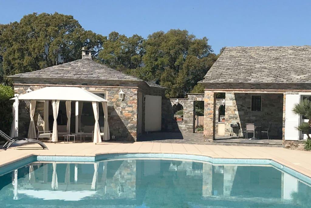 Dans propriété de 8000m2 comprenant Bergerie et dépendances : Maisonnette pierre et lauze, 2 pièces, 55m2, avec terrasse privée vue sur piscine et jardin arboré.