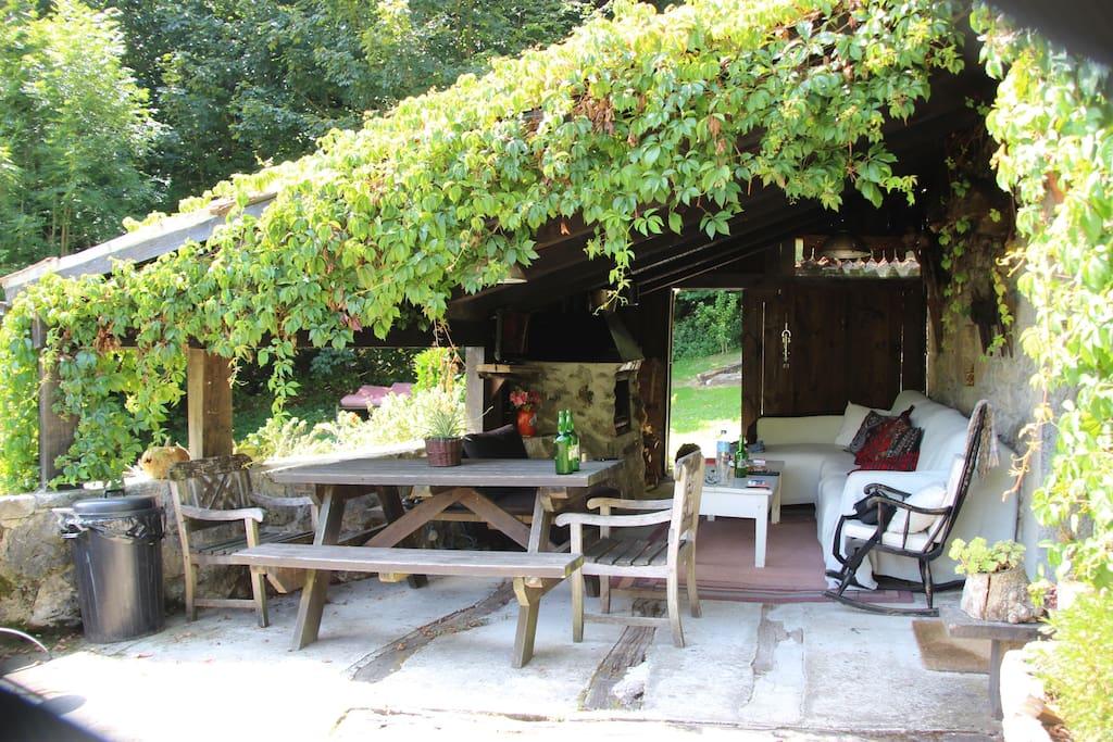 Porche con mesa de comedor,bancos,sofa y cheslonge,Tv,chimenea y leñero.