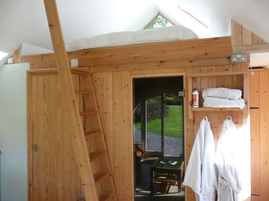 Ladder up to king sized bed above sauna