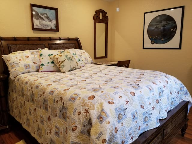 Second bedroom with a queen bed, desk and mirror. Night stand on left and 42inch TV on Chest of drawers. Large window looking onto the back yard. Ceiling fan.