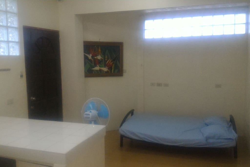 """Main door with folding bed and electric fan (this area of the home is non-airconditioned but is cool if airconditioned room is open). 21"""" LCD TV placed before guest's stay"""