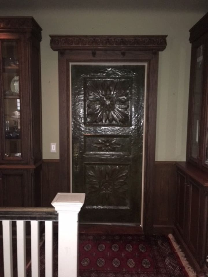 """The entrance to the Penthouse is a carved Honduras Mahogany door that was carved by the famous German  Carver, Alexander """"Chips"""" Zeller in 1967.  It is a valuable art piece as are many of the porcelains, antique furniture and paintings."""