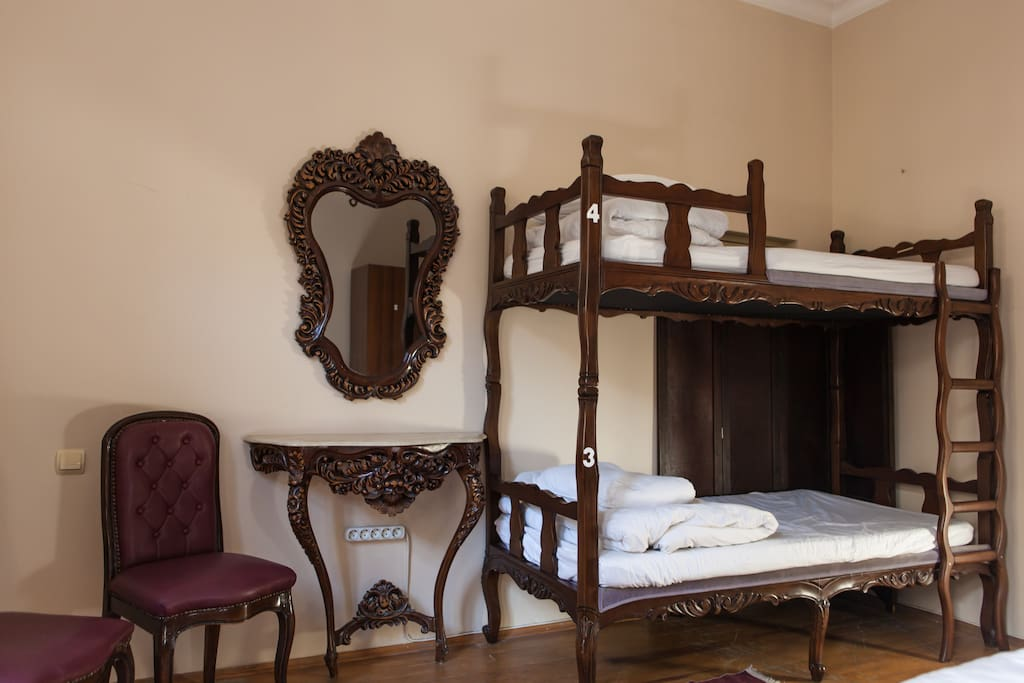 A bunk bed, mirror with a table, chairs