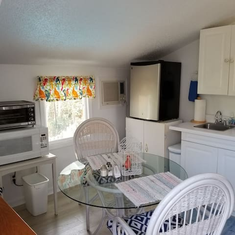 Kitchenette with fridge, sink, microwave, coffee pot, toaster. Dishes, coffee, snacks.
