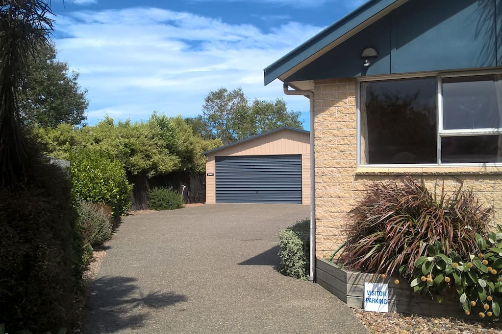 Off street parking is available at the front of the house to the right on the gravel. The pathway to the studio is marked with an arrow to the left of the garage.