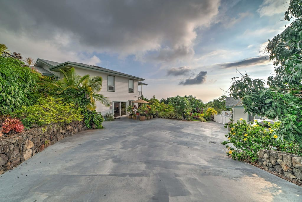 Lush gardens lined with tropical foliage and fruit orchards surround this charming home.