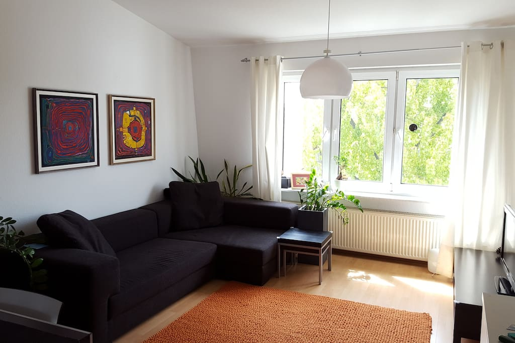 Spacious living room with cosy couch, flat screen TV and cable