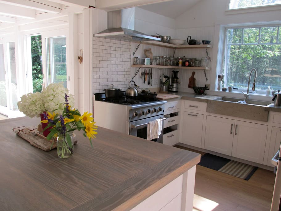 Custom Kitchen with prof. gas range, cement counters, extra deep sink, dishwasher, open shelving.