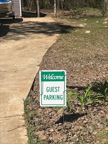 Park your vehicle by this parking sign or farther down the drive. Trailer parking is available in this area. Do not park up by the garage! Do not park in the grass! You will be blocking our truck - it is only used occasionally.