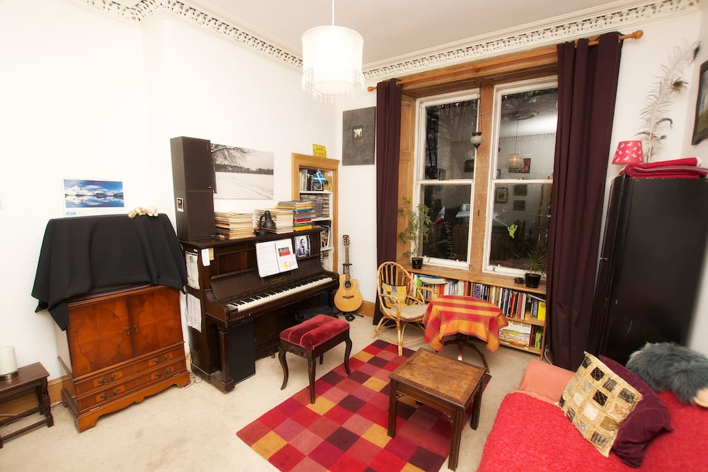Sitting area of your room with piano and large sash window
