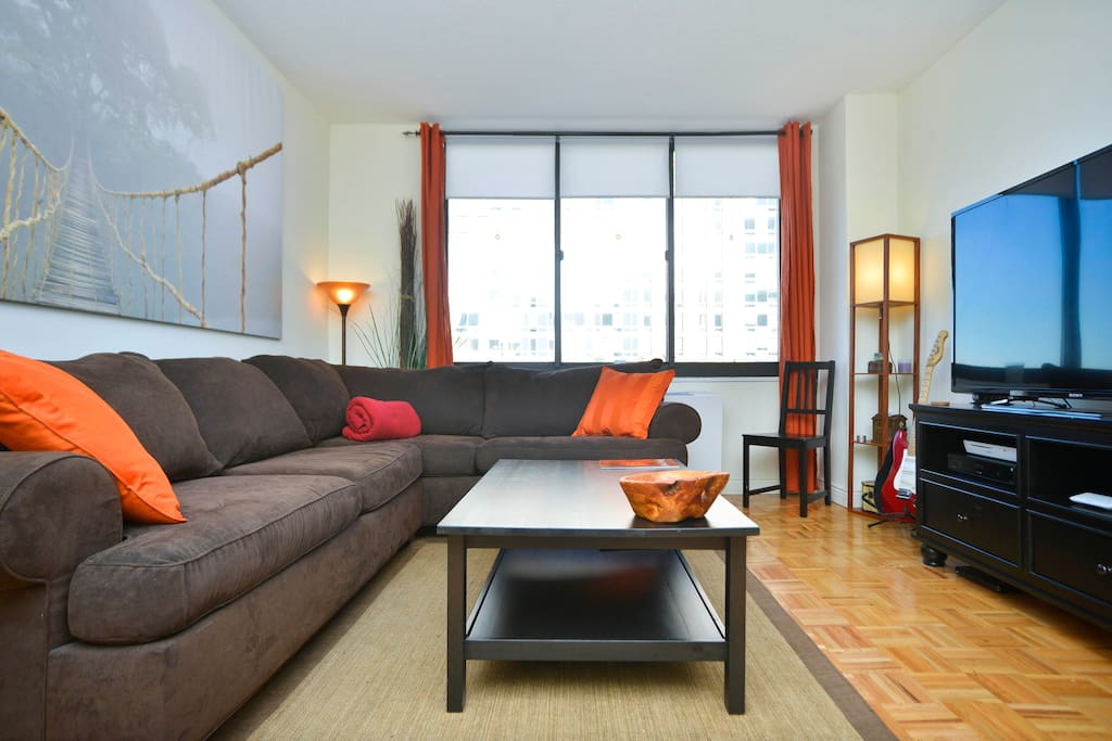 Huge comfortable L shaped couch in the living room with large windows and plenty of light, flat screen TV