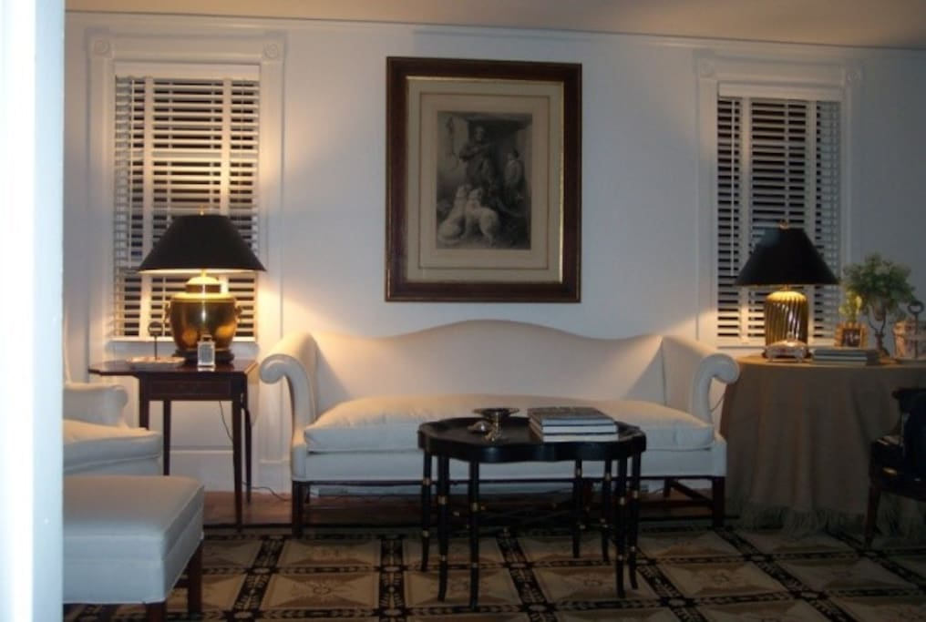 Elegant, comfortable living room with fireplace, antiques, and wonderful vintage paintings.