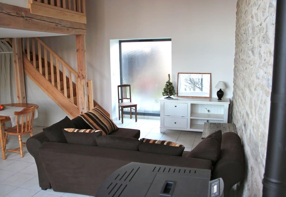 Salon du gîte (coin canapé/télé, poêle à granulés, salle à manger)