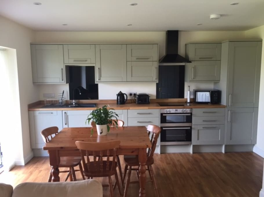 Integrated appliances include dishwasher, double oven, fridge, microwave. French doors to lake & lawn