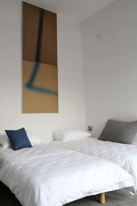 View of two single beds in Writer's room with owner's art work on the wall!