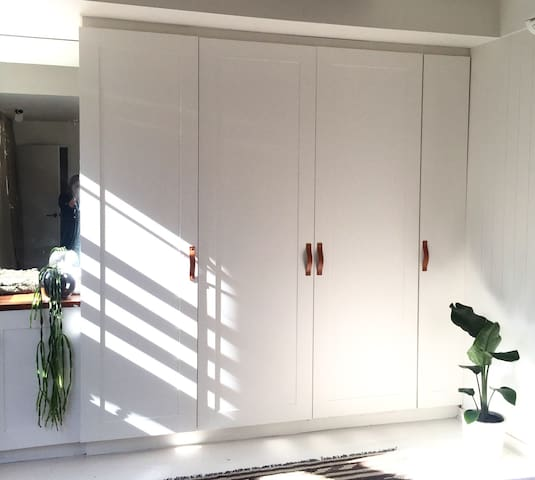 Large wardrobes in the garden studio with leather and brass handles. Indoor plants and lots of natural light. Linen curtains. Aircon and heating. Ensuite bathroom. King bed