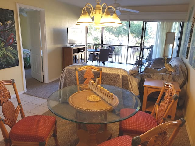 Living room with open kitchen and tropical views - smart TV features Netflix, HBO, Amazon prime