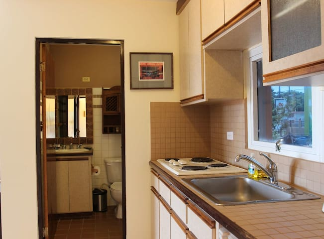 fully stocked kitchen with 1/2 size refrigerator, stovetop, microwave, coffee maker, pans, plates, cooking utensils